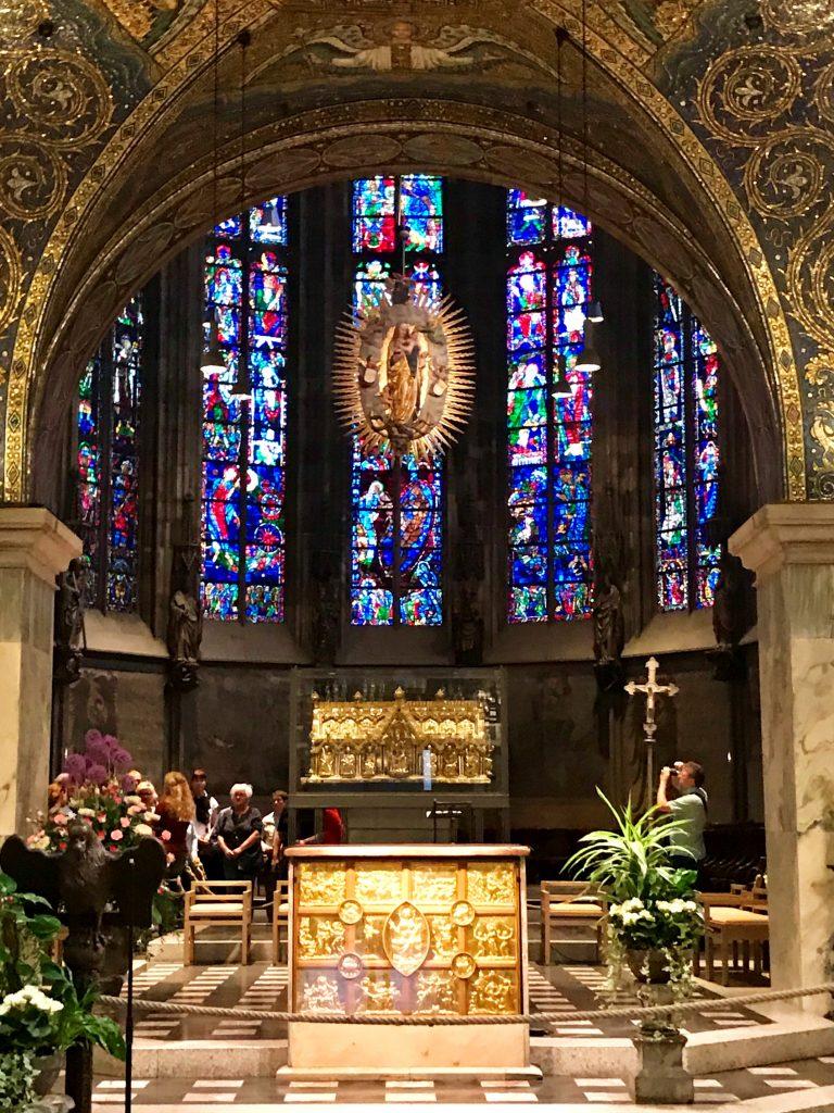 Im Altarraum des Aachener Dom leuchten die bunten Fenster.